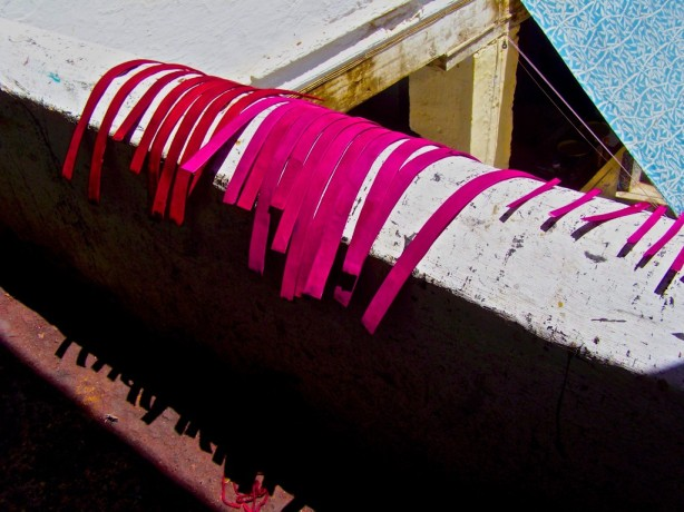 Newly dyed leather hangs from a railing in Fez, Morocco.
