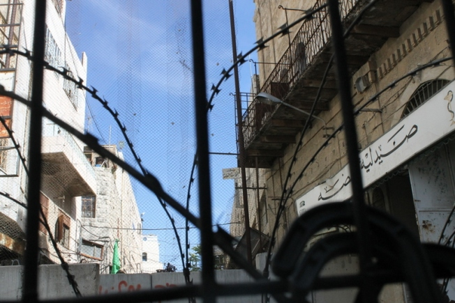 A fence separates Israel settlers from Palestinians